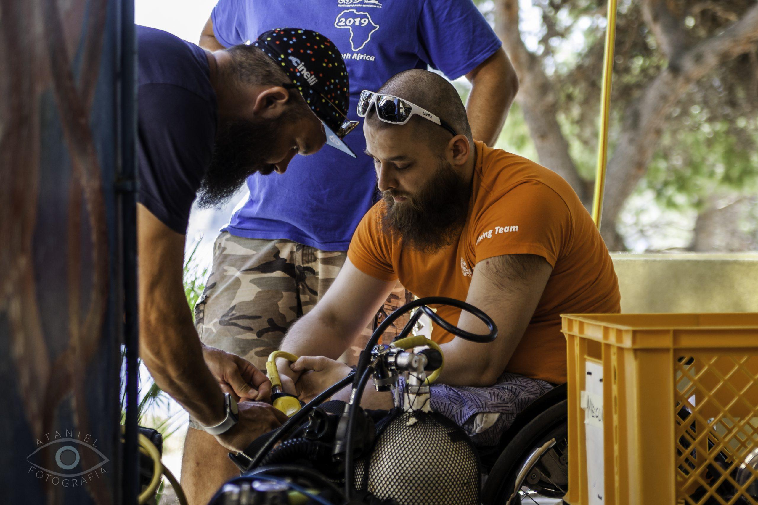 Męzczyzna na wózku montuje sprzęt nurkowy. Obok pochyla się drugi, pomagając mu.